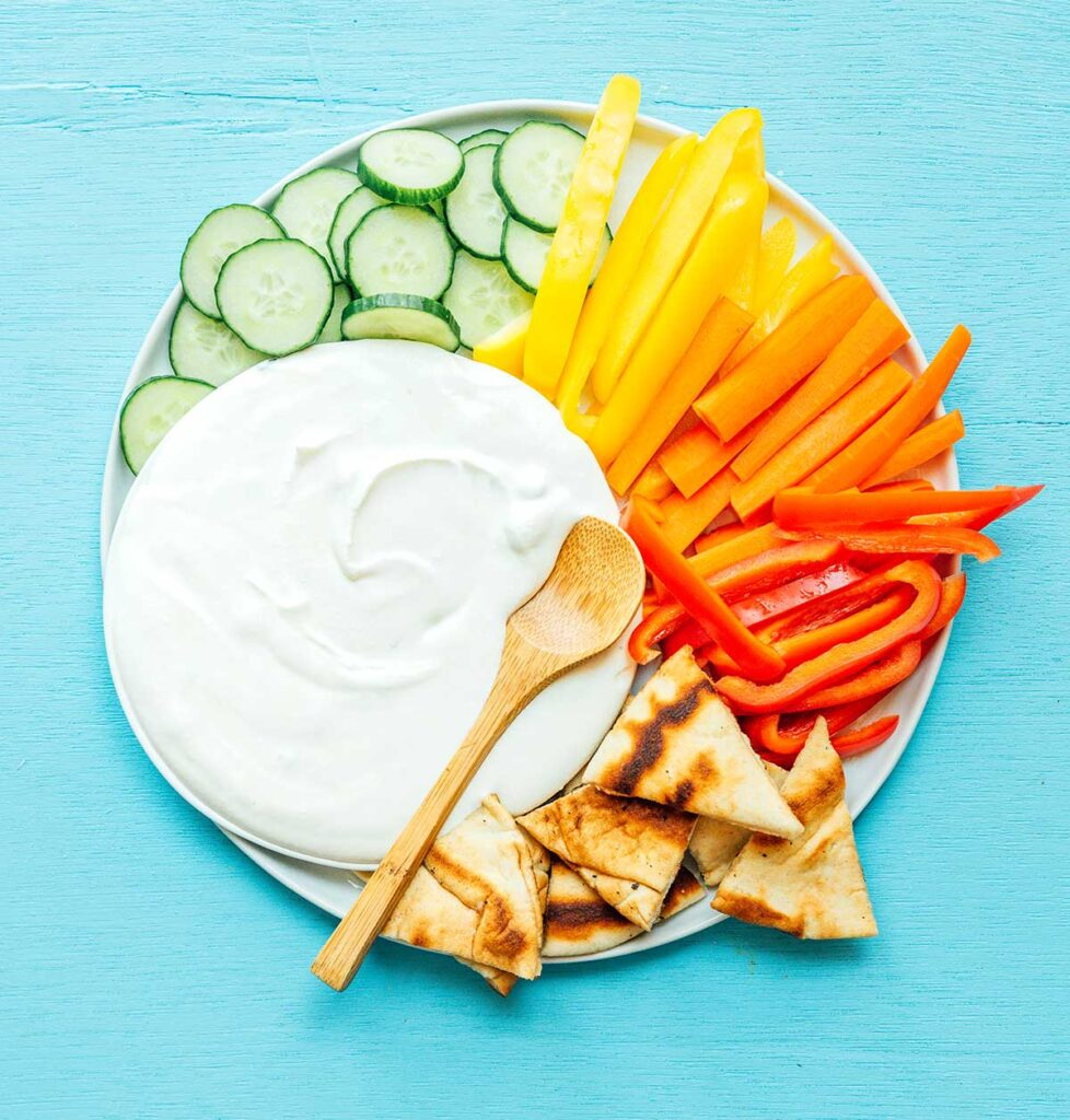 A bowl of whipped feta spread on a white plate surrounded by sliced cucumbers, sliced bell peppers, and pita bread
