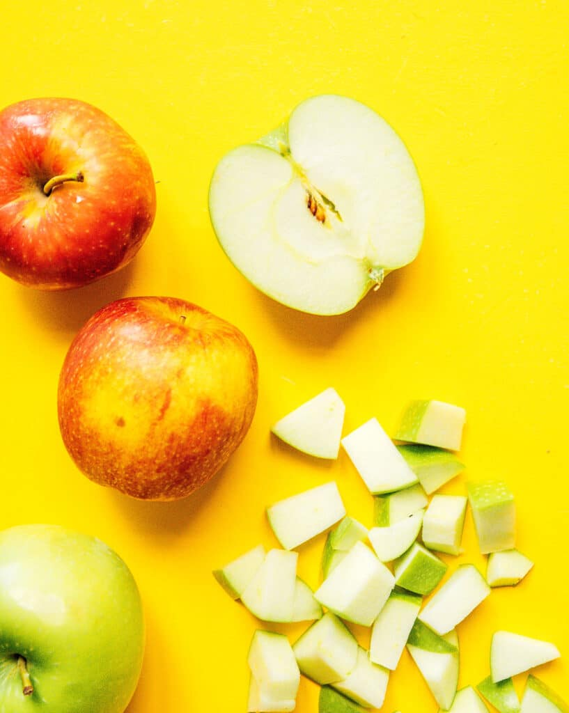 Three whole apples, an apple half, and diced apple pieces arranged on a yellow background