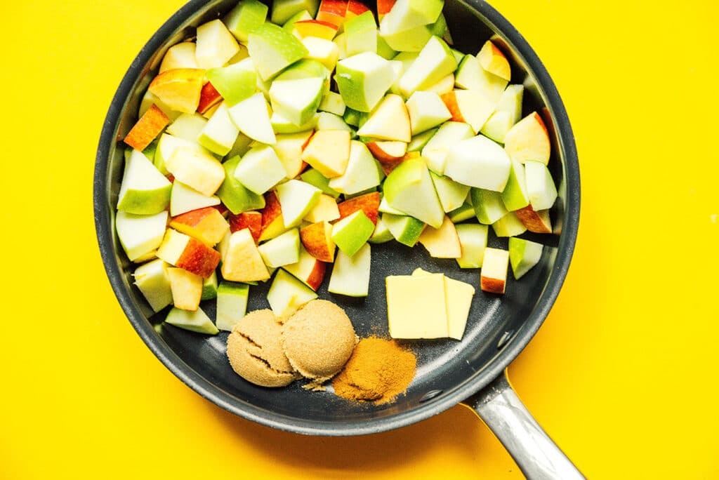 A pan filled with diced apple pieces, brown sugar, butter, and cinnamon