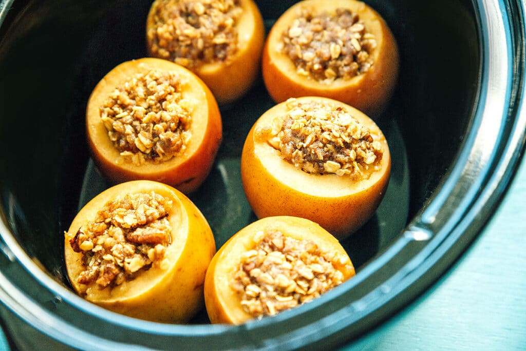 A slow cooker filled with 6 stuffed apples