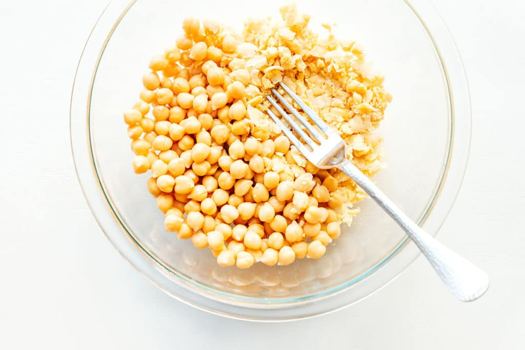 A clear glass bowl filled with chickpeas, some of which have been mashed with a fork